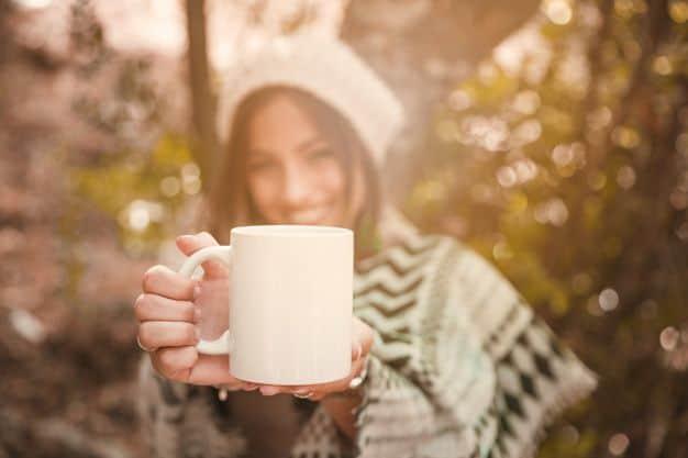 una mujer borrosa enseñando una taza en el bosque
