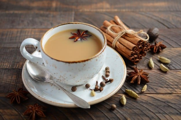 taza de masala chai con leche en una mesa de madera