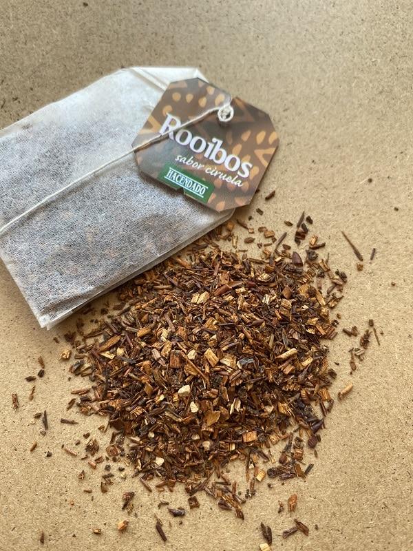 Una bolsita de té rooibos Mercadona junto a su contenido interior esparcido sobre una mesa