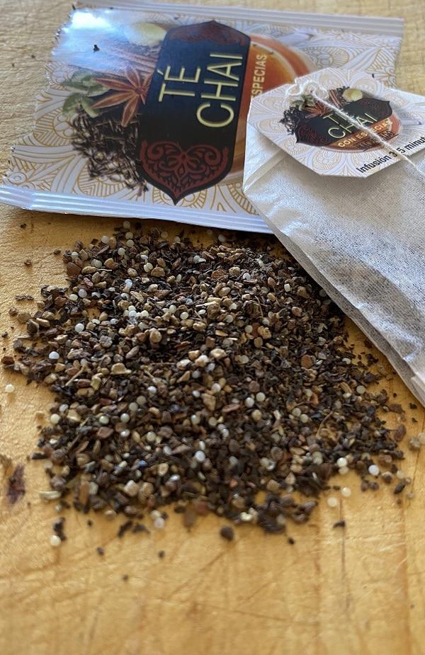 Una bolsita de té chai Mercadona junto a su contenido interior esparcido sobre una mesa