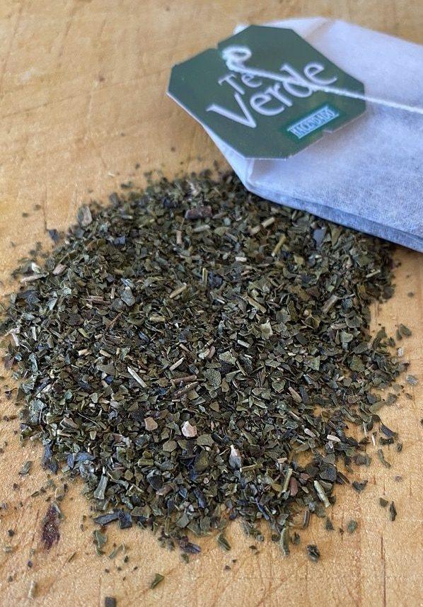 Una bolsita de té verde de Mercadona con el contenido interior esparcido sobre una mesa