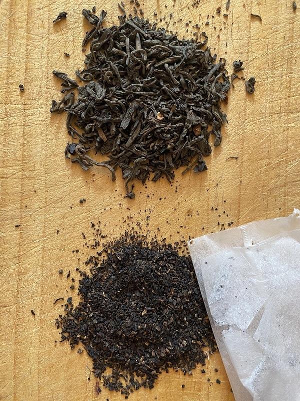 Un puñado de hojas sueltas de té arriba y el contenido de una bolsita de té abajo para comparar.